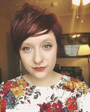 An image of a white woman with short red hair, wearing a floral shirt